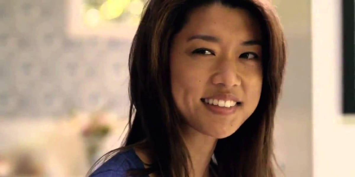 Kono smiling and looking to her right, wearing a purple shirt in Hawaii Five-0