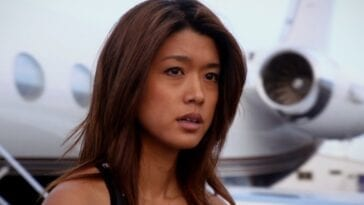 Kono looking somewhat contemplative and annoyed, looking to her left, with a plane in the background in Hawaii Five-0