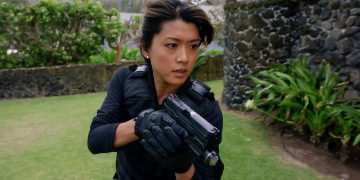Kono holding a gun and wearing a vest, looking straight ahead, an intense look upon her face in Hawaii Five-0