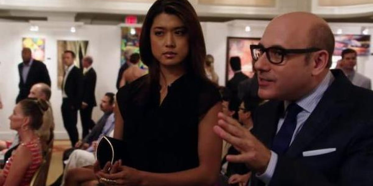 Kono and Gerard Hirsch in Hawaii Five-0, Kono wearing a dress and looking speculatively ahead, with Gerard talking and holding up his hand in Hawaii Five-0