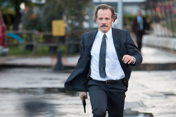 Agent Shepard runs towards the scene with a gun drawn.