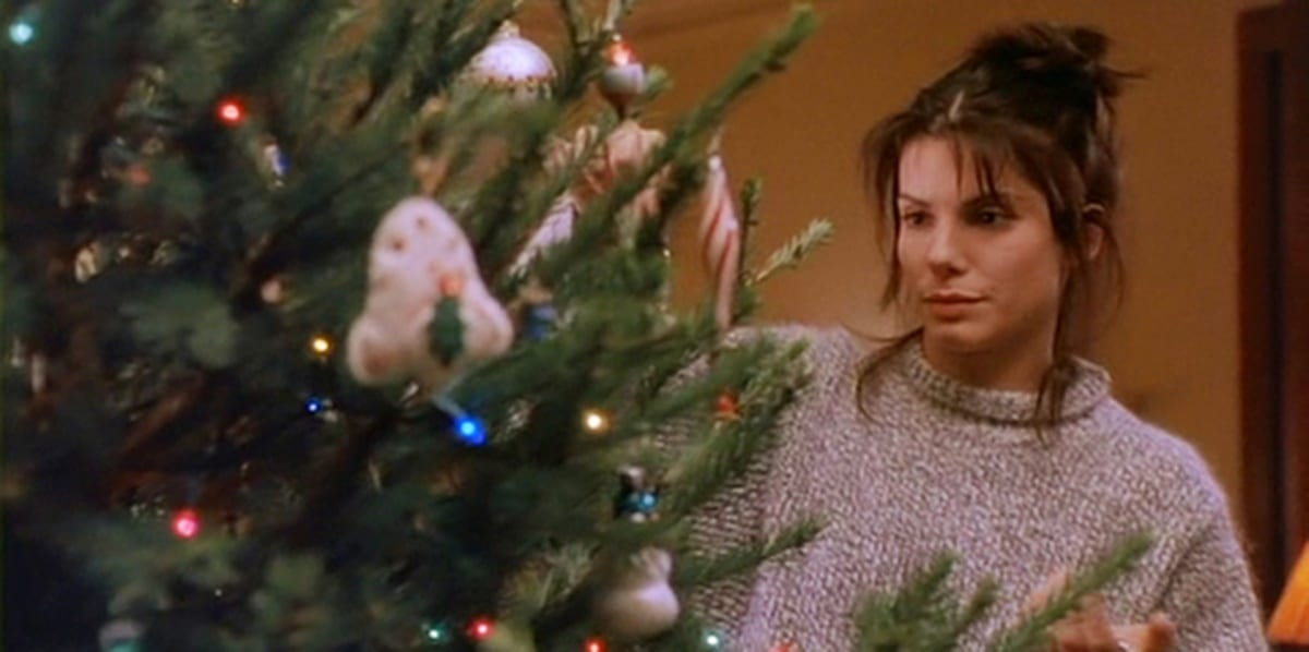 Lucy decorating her Christmas tree, wearing a grey sweater