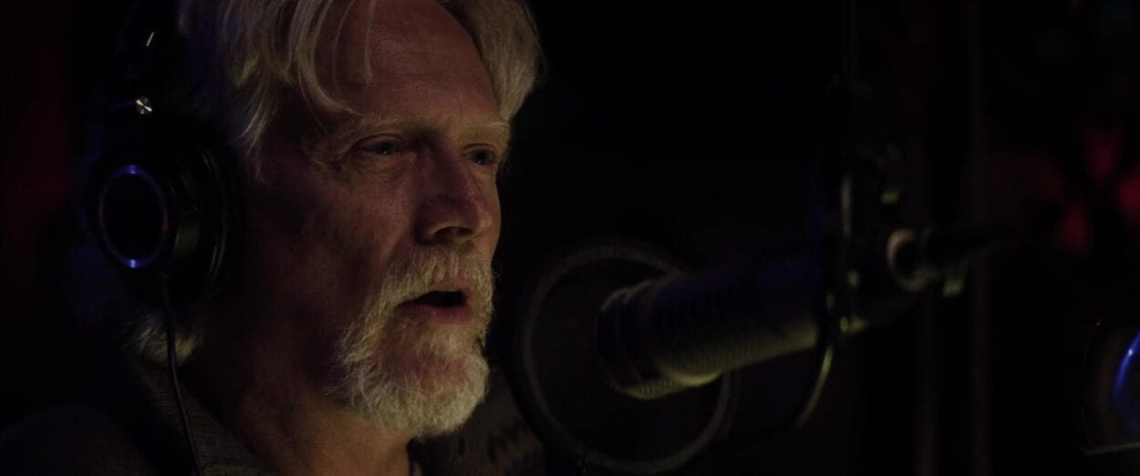 older man sits in a darkened room in front of a microphone set-up