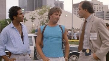 Tubbs and Crockett standing and looking at their Captain in Miami Vice, Tubbs has a hand in his pocket and Crockett has his head to the side and his lips pursed