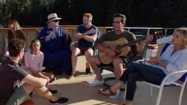 "Left to right: Luke, Lily, Gloria, Cam, Mitchell, Phil on guitar, and Claire in Modern Family's ""Lake Life"" while sitting on the top deck of a houseboat overlooking a lake"
