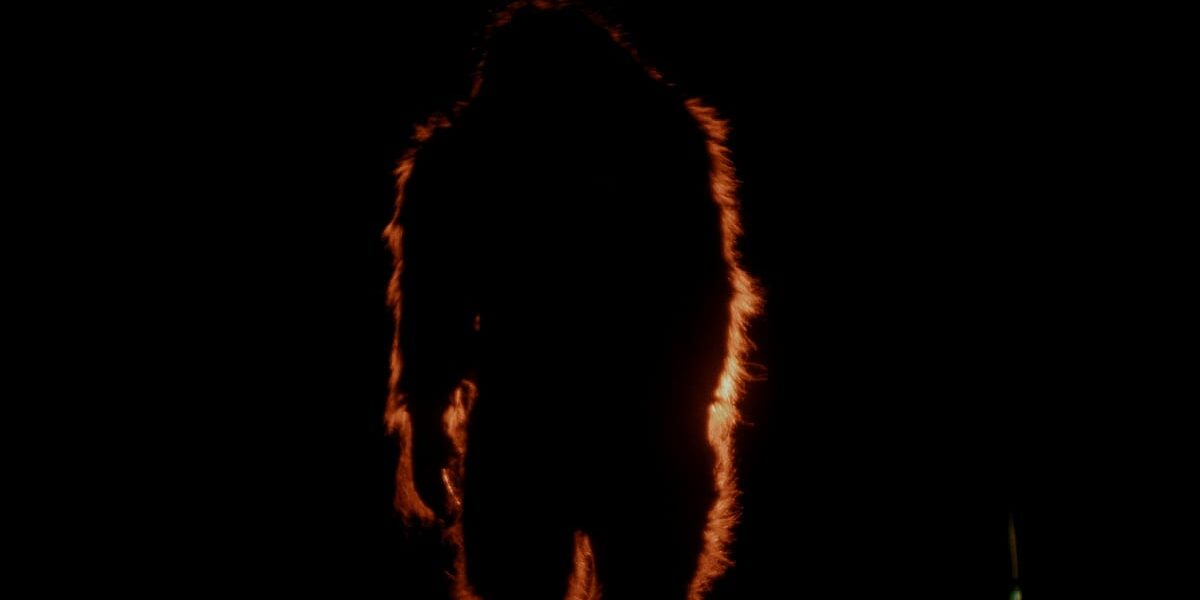 Bigfoot stands in the darkness, highlighted with a dash of light in the distance.