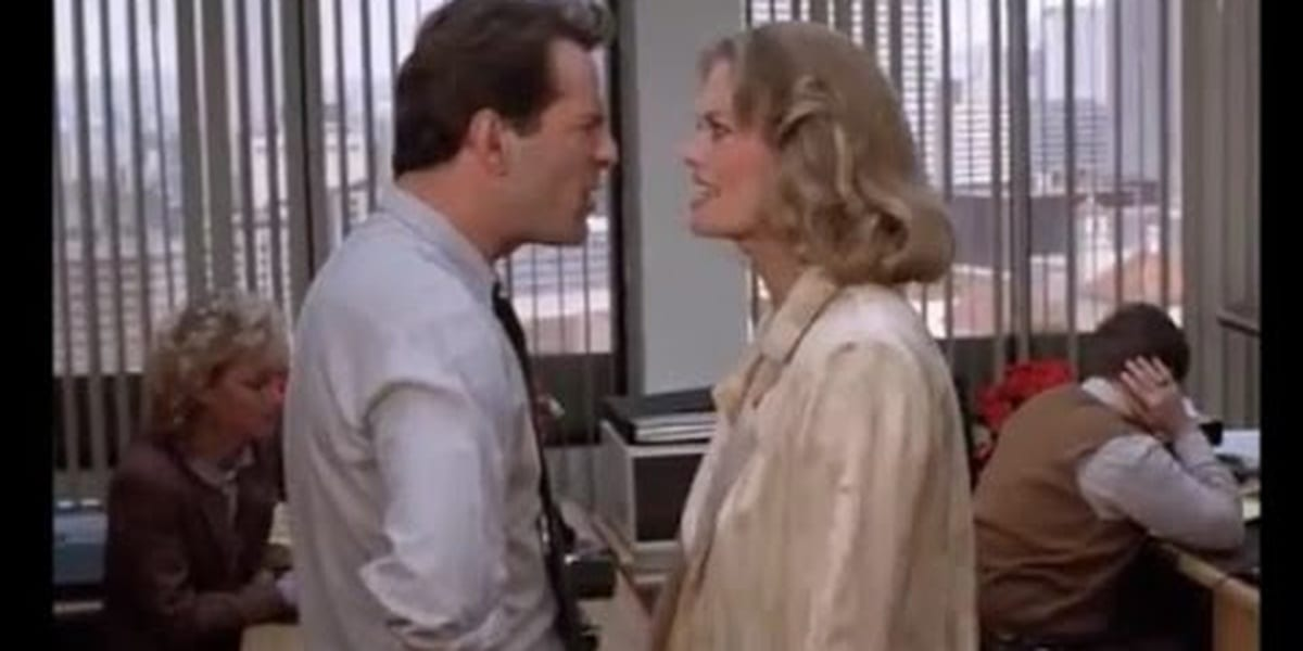 David and Maddie in one another's faces, their expressions contorted into anger as they argue, people in cubicles in the background, one man covering his ear in Moonlighting
