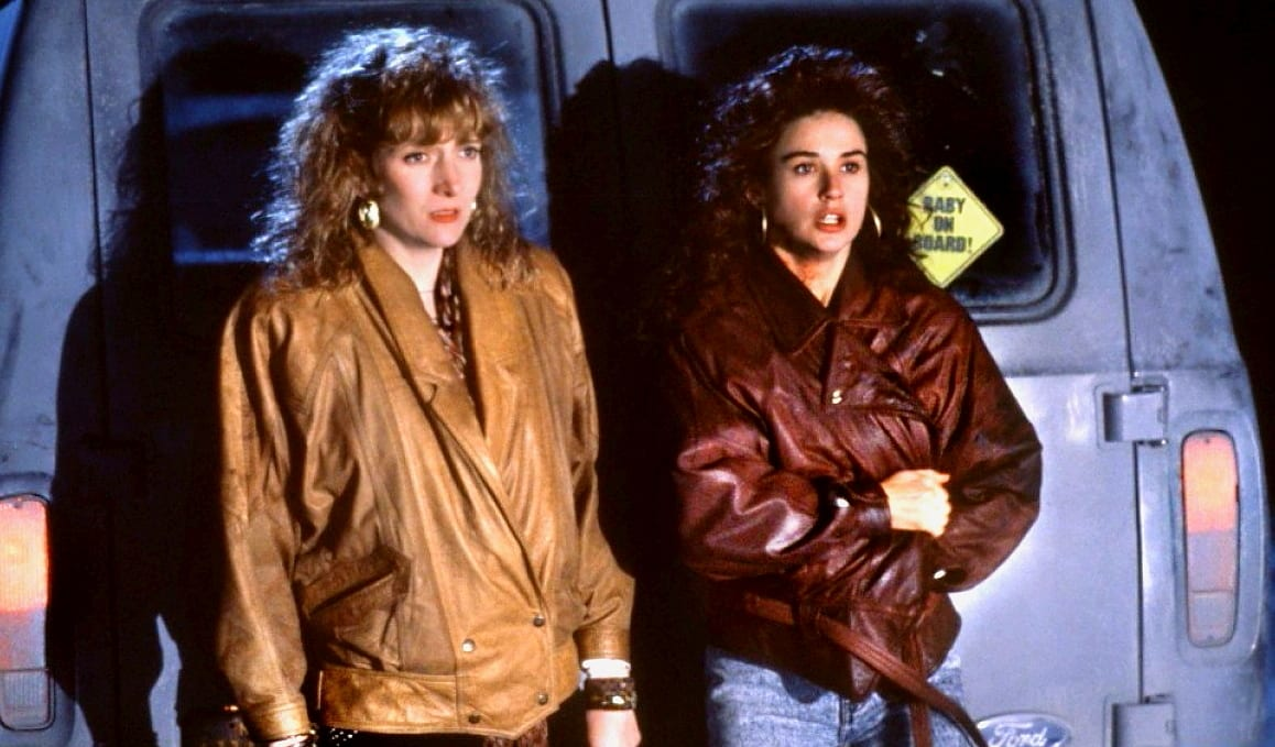 Joyce and Cynthia stare in fear against a van as a car's headlights drive toward them at night