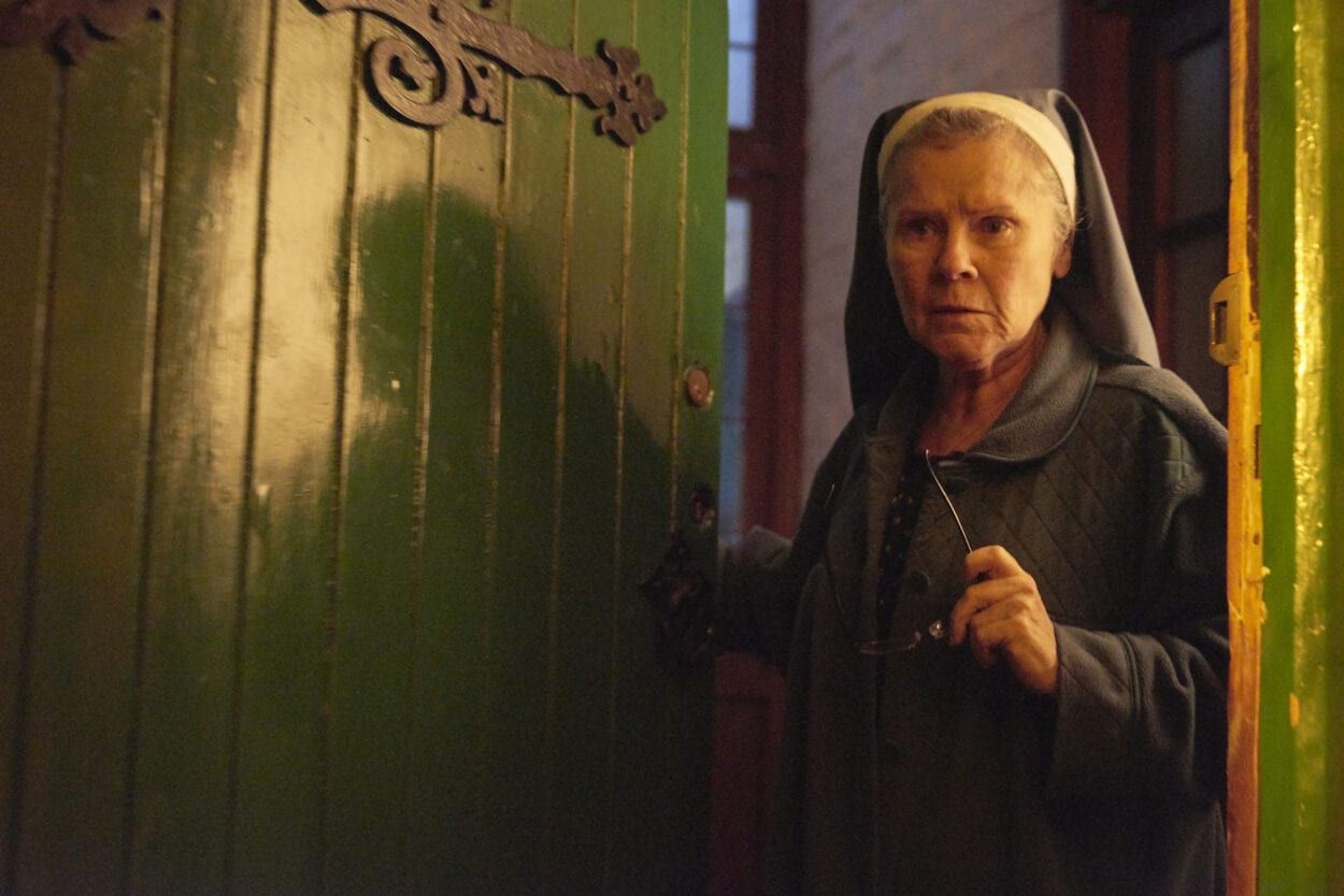 A nun wearing a habit and holding spectacles holds open a green door and looks out suspiciously.