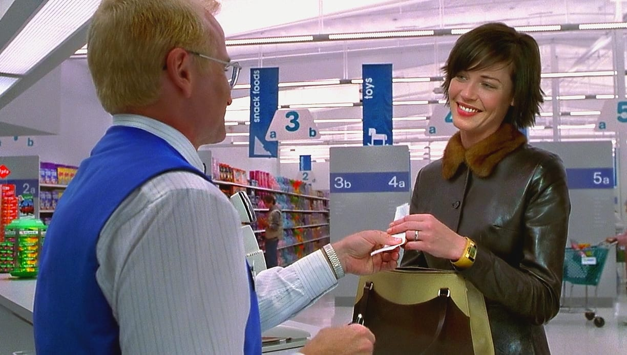 """Sy """"The photo guy"""" hands a receipt to Nina Yorkin in a department store"""