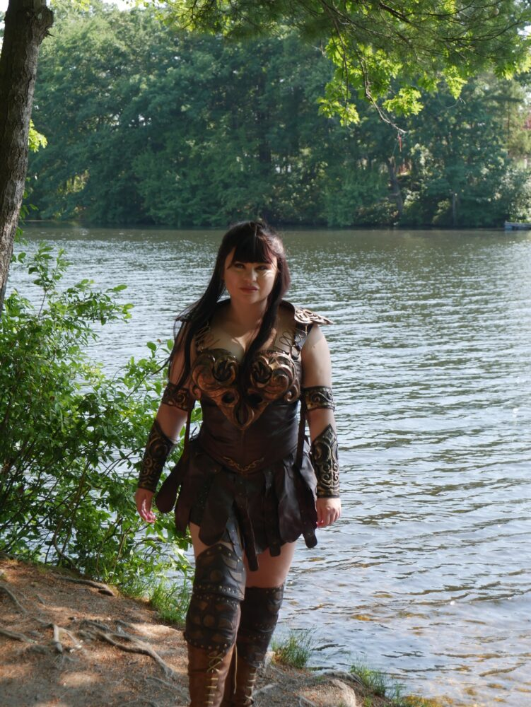 Xena cosplayer in front of a wooded lake