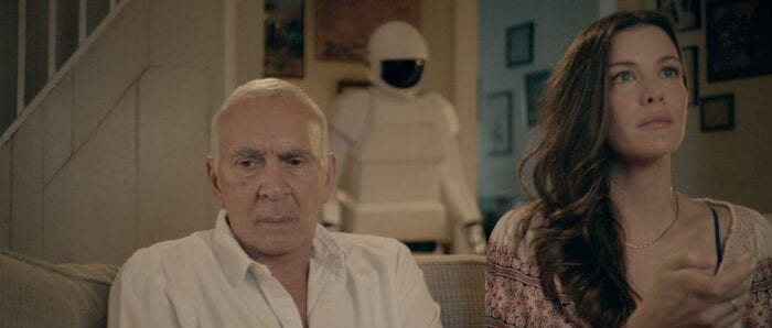 Frank looks away from Madison while she watches television with the robot behind them.