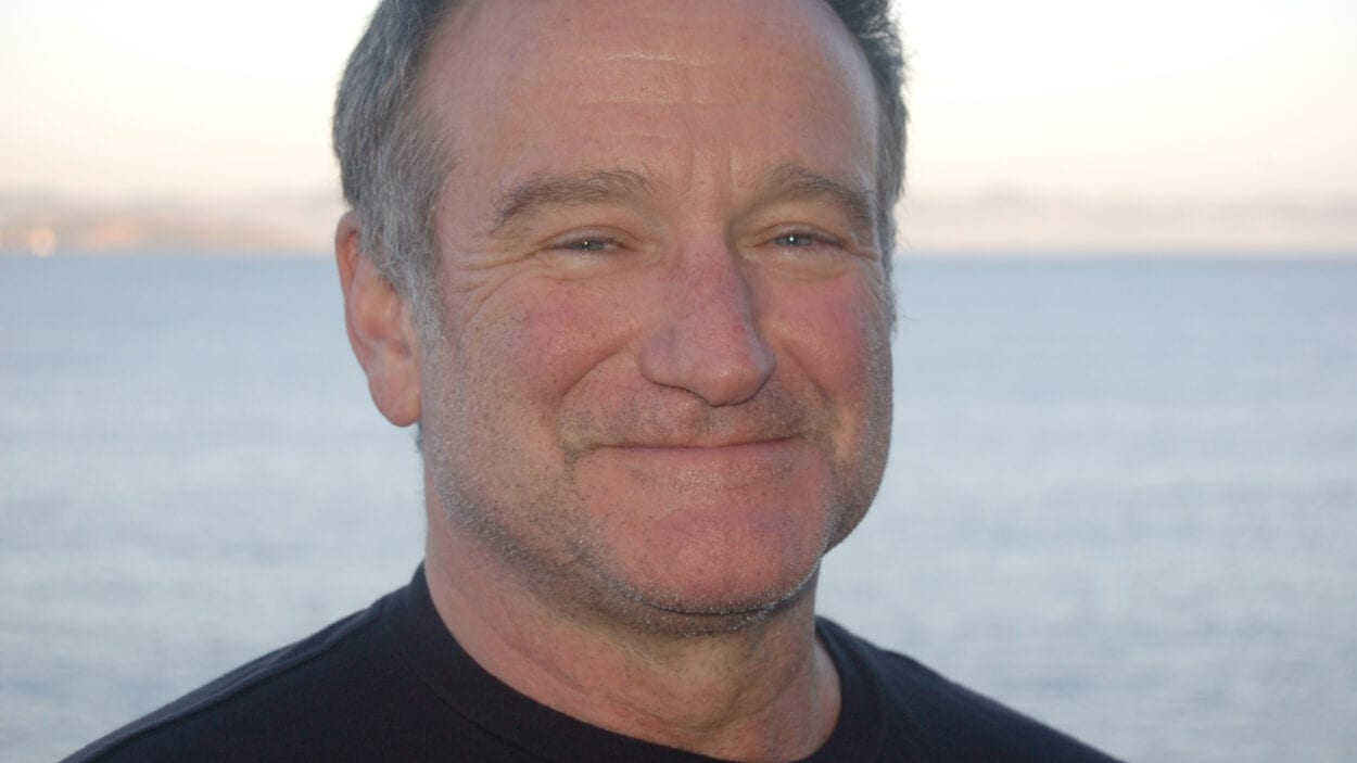 Robin Williams smiling in front of the ocean.