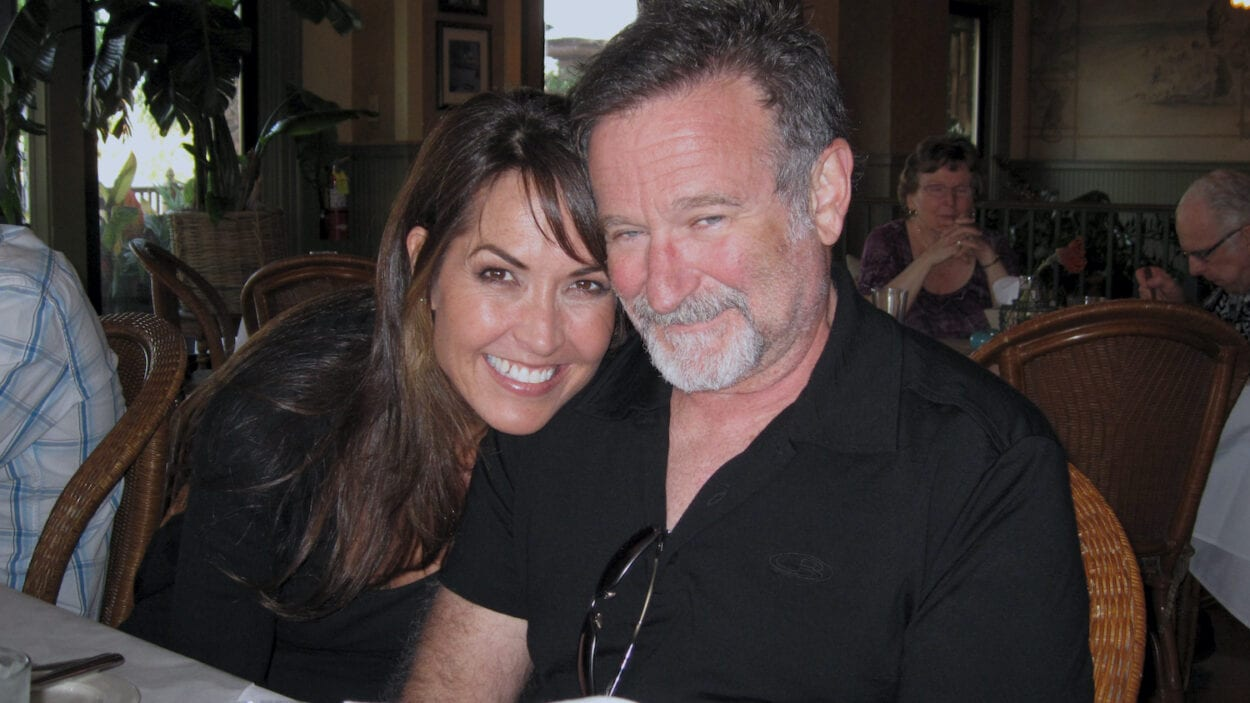 Susan Schneider Williams and Robin Williams pose for a photo, smiling.