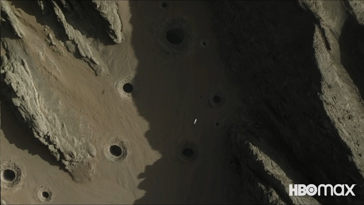 A small spacecraft flies low over a desert valley full of serpent pits
