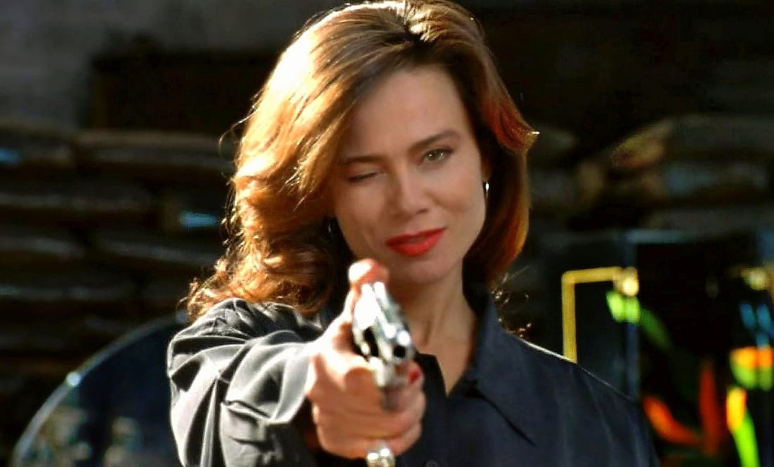 Mona Demarkov smiles and winks while pointing a gun straight ahead