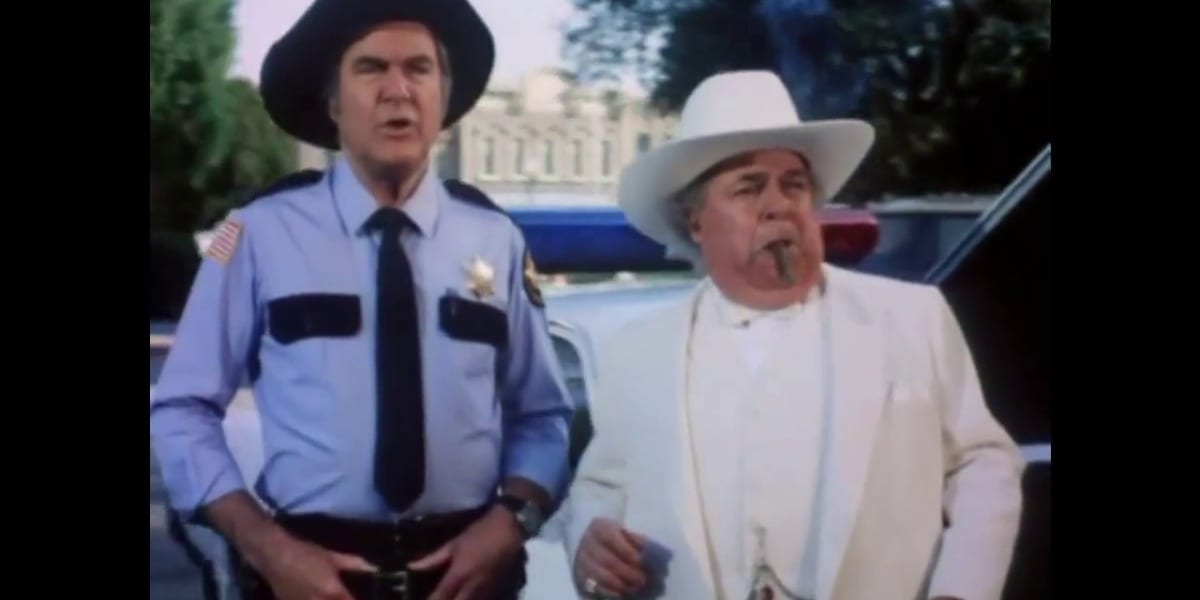 Rosco with his hands on his belt, mouth open as he speaks, with Boss standing next to him, a cigar in his mouth in Dukes of Hazzard
