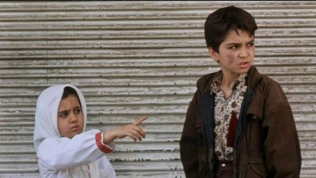Razieh points to something offscreen while her brother Ali looks in the same direction.