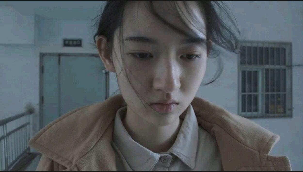 A close-up shot of Huang Ling's (Uvin Wang) as she's standing outside the door of an apartment building.