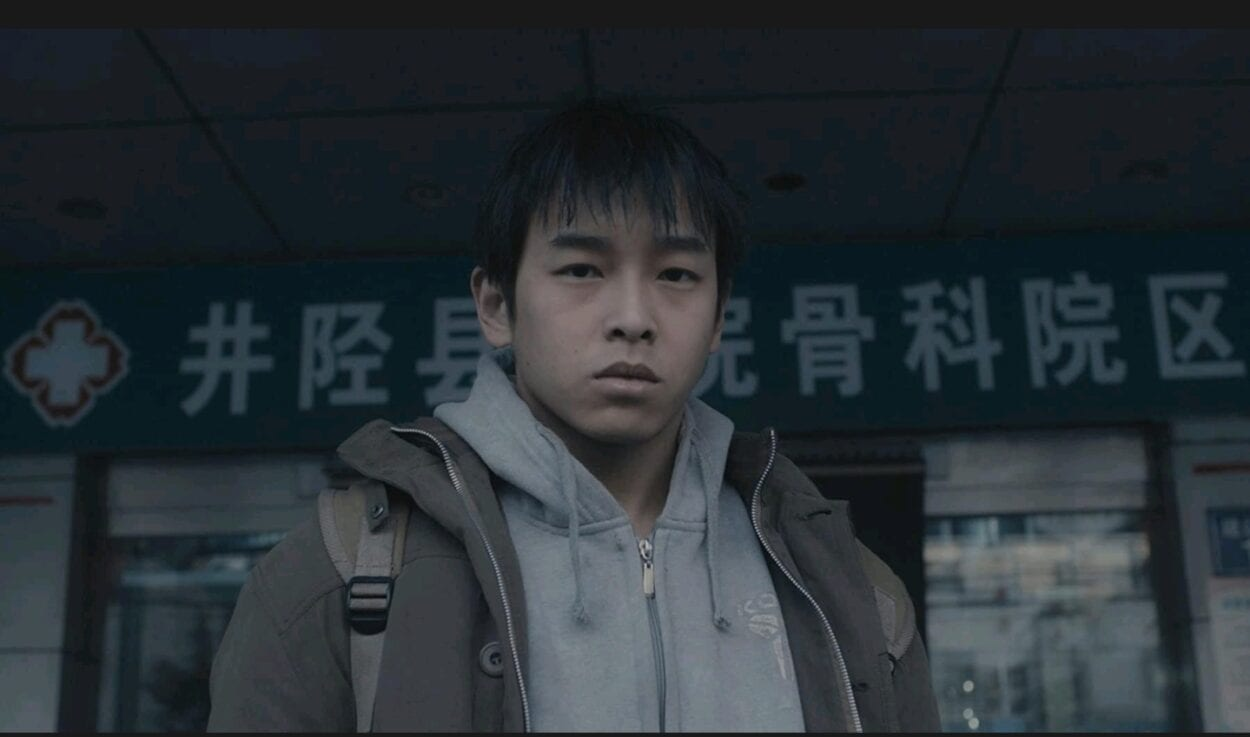 Wei Bu (Yuchang Peng) stands outside the door of a building as he looks into the camera
