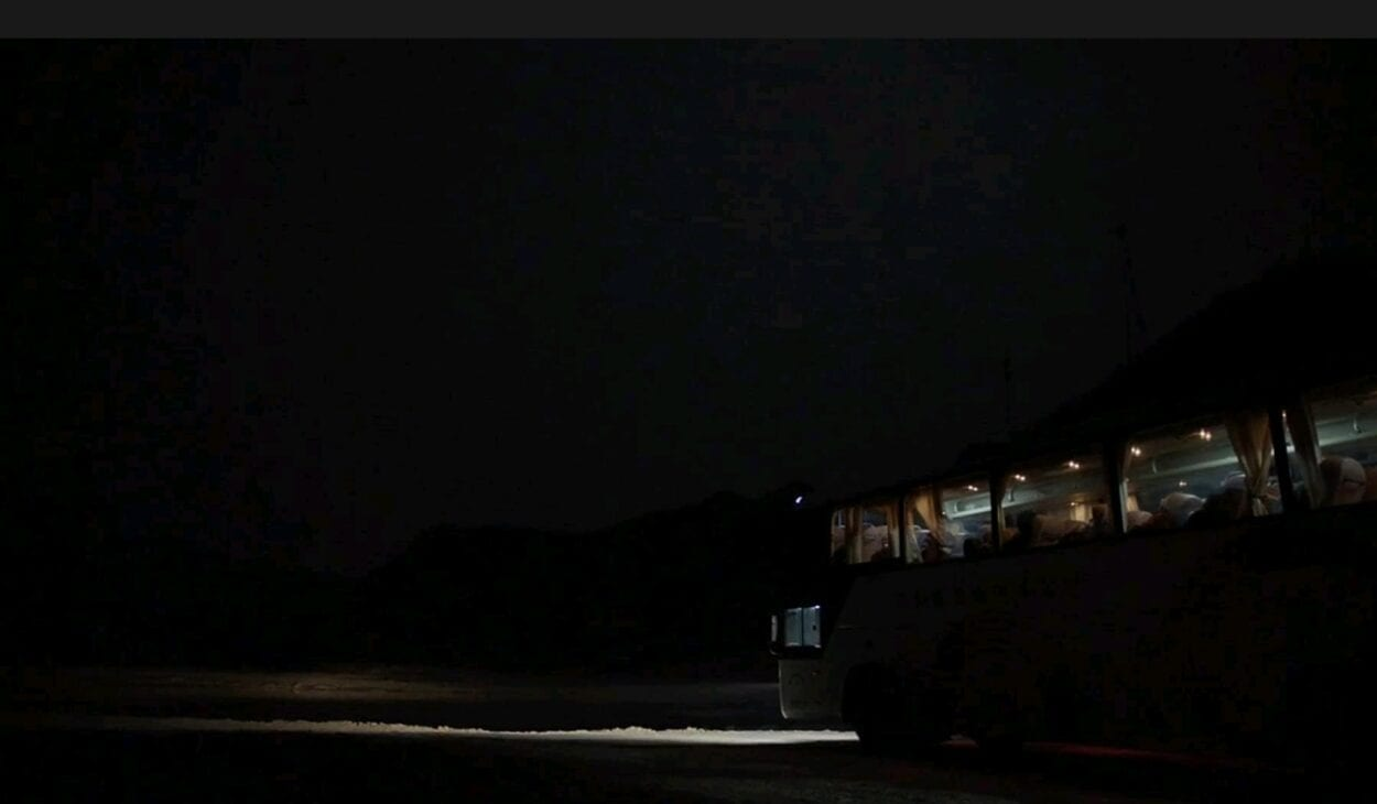 A bus is still in the middle of a dark road with the headlights on