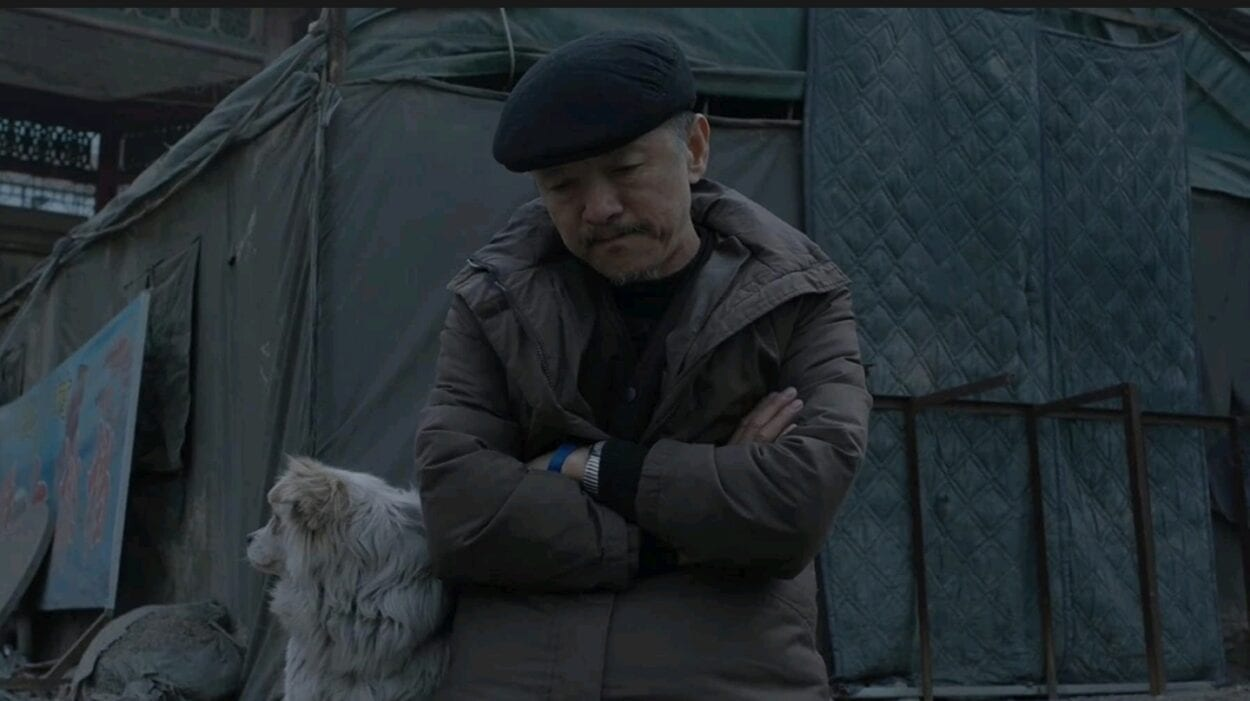 Wang Jin (Zi Xi) sits outside arms-crossed with his dog at his side