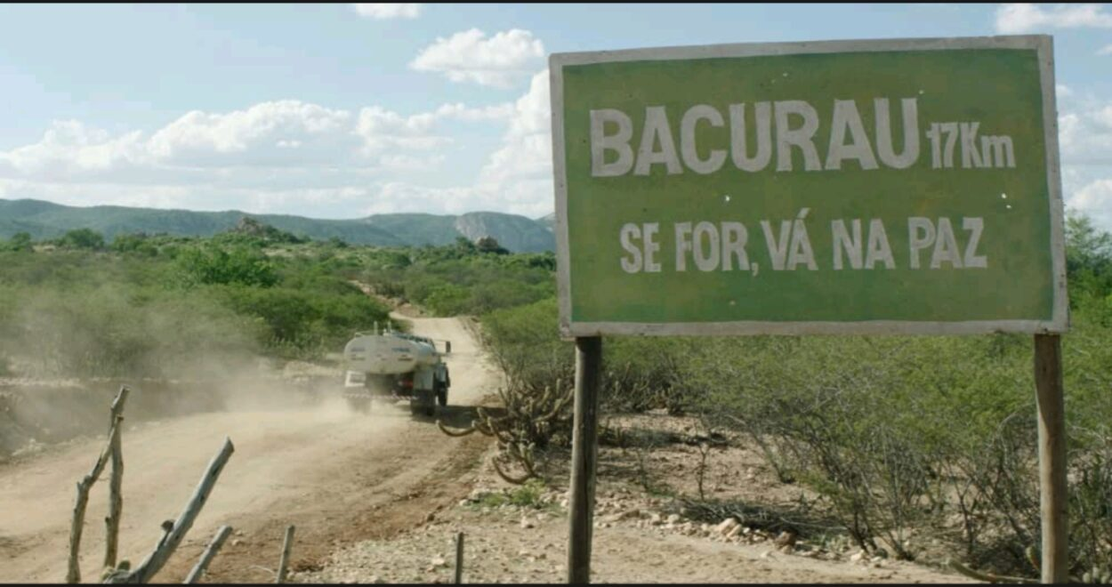 "A medium shot showing a car driving past a signpost of Bacurau with a Portuguese sentence underneath the town's name stating ""If you go, go in peace"""