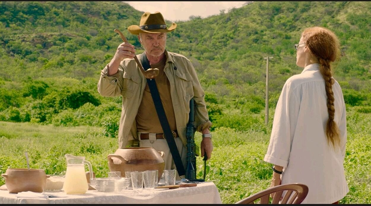 A medium shot of an armed Michael (Udo Kier) and Domingas (Sônia Braga) as they face each other at a table with potted stew and cashew milk