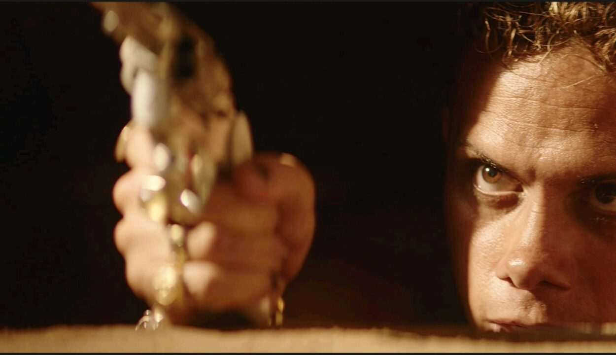 A close-up shot of Lunga (Silvero Pereira) aiming a revolver from underneath the concealed floorboard of a house