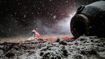 Konstantin Veshnyakov sits on the ground near Oorbiter-4 as the snow falls and blankets the area