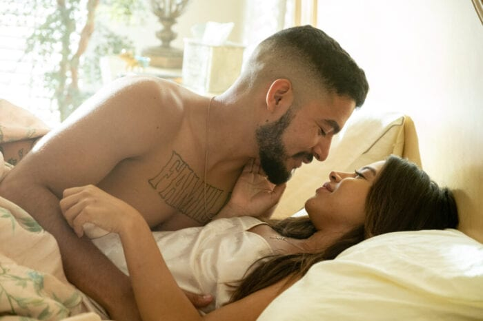 A shirtless David embraces his lovely wife in bed.