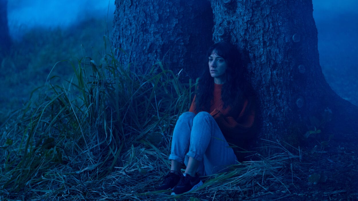 Mina (Sheila Vand) cowering behind a tree in a blue-lit fog-ridden forest.