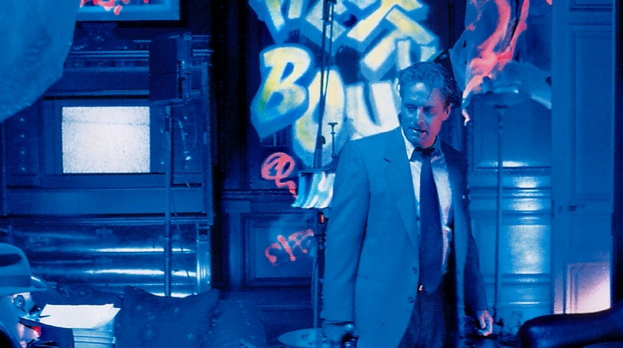 Nicholas Van Orton stands in a strange blue lit graffiti covered room