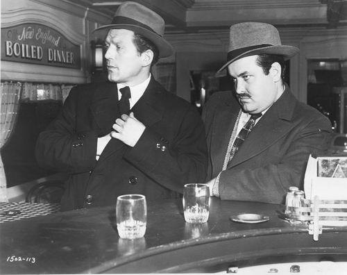 Two hitmen sit at a diner counter, looking to their right offscreen