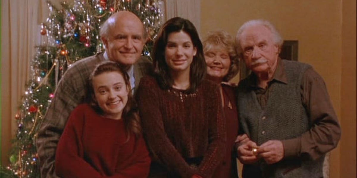 Lucy stands in the middle of a family picture, Peter's parents behind her, his godfather to her left, and Peter's sister to her right with a Christmas tree in the background