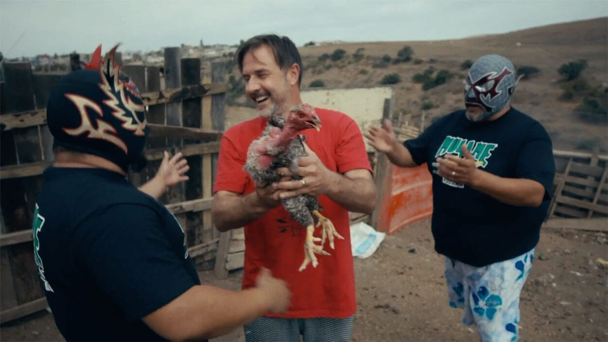 David Arquette standing in the Mexico desert, holding a chicken, surrounded by two luchadors.