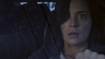 Jessica (Jules Wilcox) driving her car, appearing shocked.