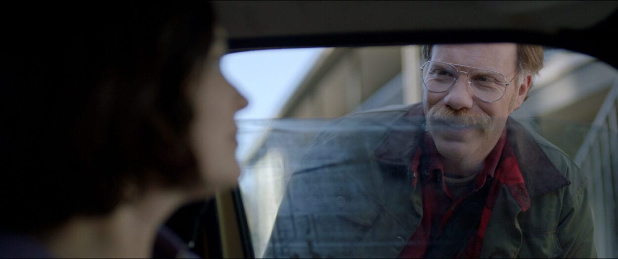 The Man (Marc Menchaca) peering into Jessica's (Jules Wilcox) car.