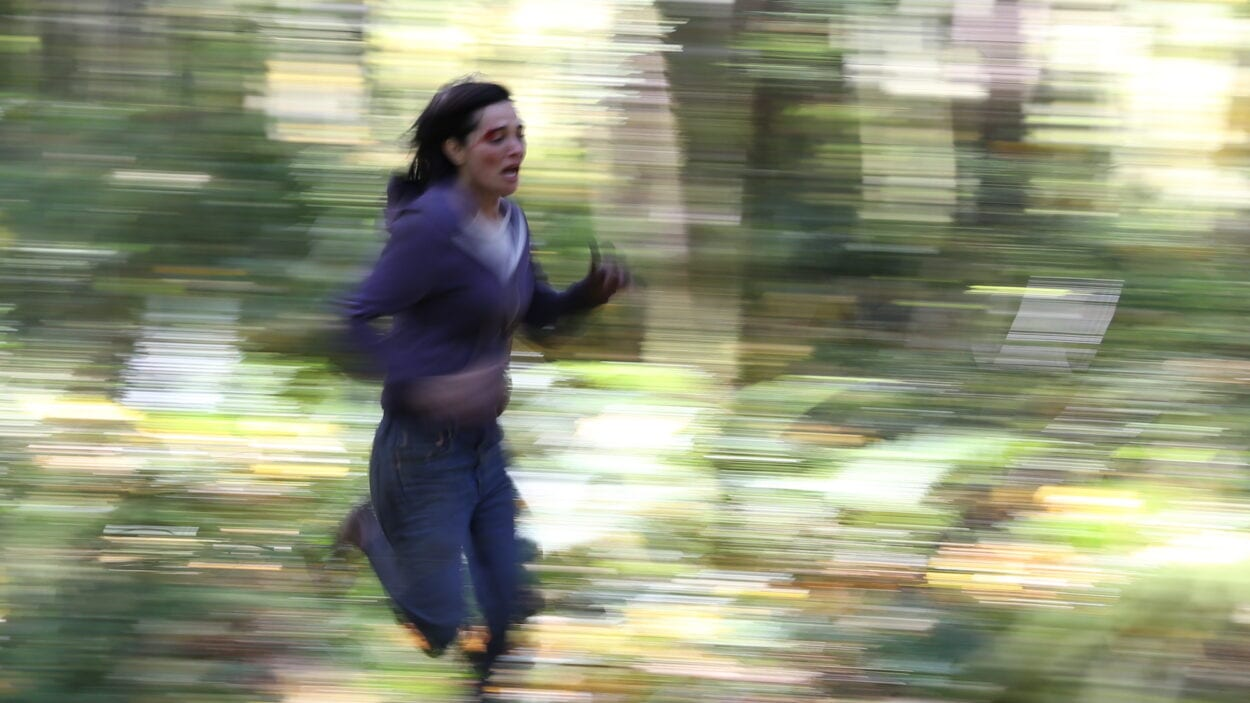 Jessica (Jules Wilcox) running through the woods. The photo is blurred to indicate speed.