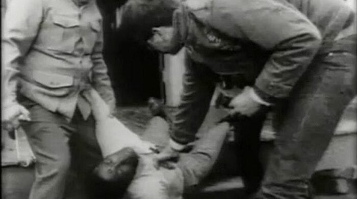 A group of men, baling hooks in hand, move Ben's dead body, bullet hole in his forehead clearly visible, out the door and down the porch steps.