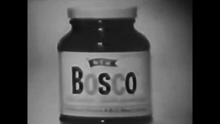 A short, squat, clear glass jar (dark chocolate syrup visible through the glass) with a white lid and white label (Bosco emblazoned across it).