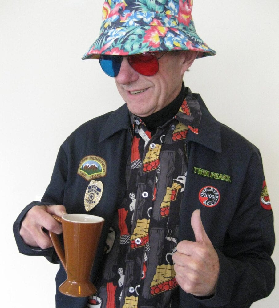 Bruce Phillips, dressed in Jacoby blue/red glasses, bucket hat, Twin Peaks hawaiian style shirt, and coat filled with Twin Peaks patches.
