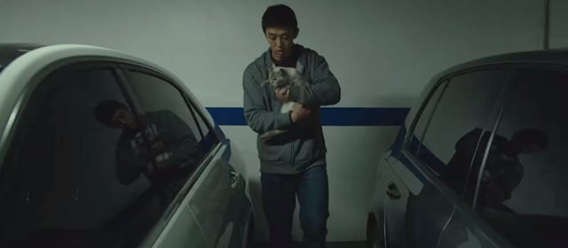 Lee Jong-su, positioned between two cars, holds a cat in his arms