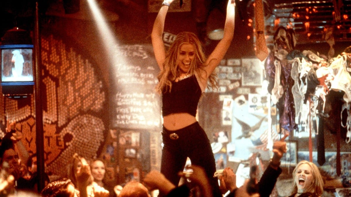Violet Sanford (Piper Perabo) stands atop a bar, arms extended in celebration of her latest performance.