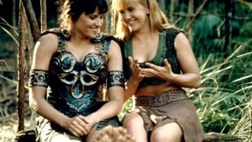 Xena and Gabrielle sit together, laughing