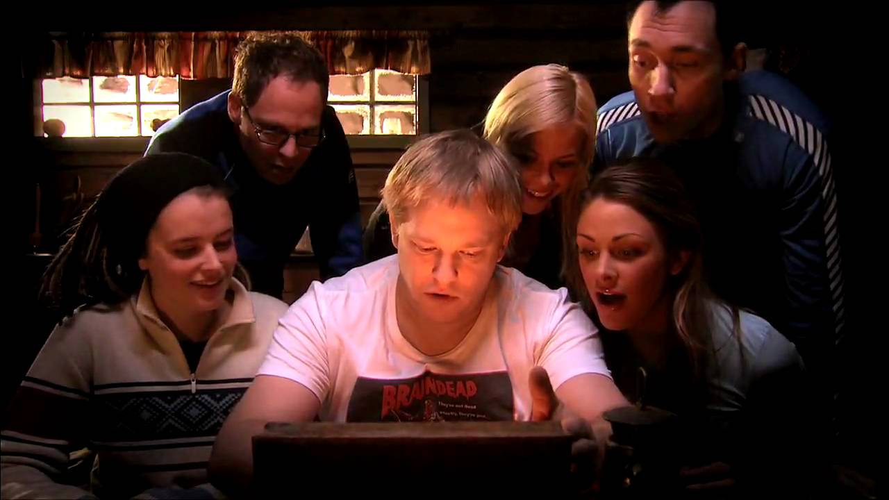 A group of six friends in a cabin crowd around a box that emits light with looks of excitement.