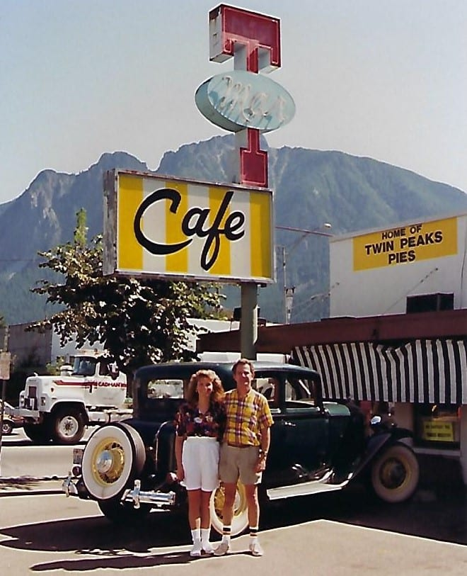 two people standing in front of a classic car, parked by the classic Double R sign at Twede's Cafe.
