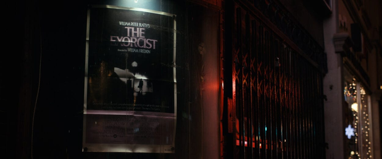 A promotional poster for The Exorcist on the side of a building late at night.