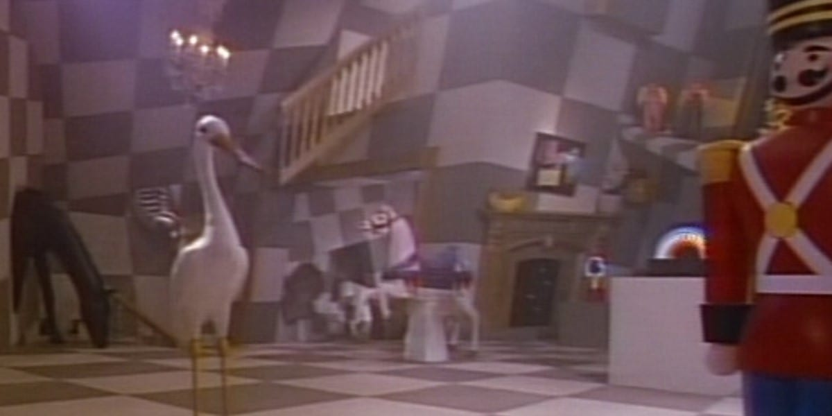 toys of a stork and a life-size nutcracker stand in the foreground of a black and white checkerboard room with warped corners and a staircase to nowhere over a warped fireplace. More toys also appear in the background.