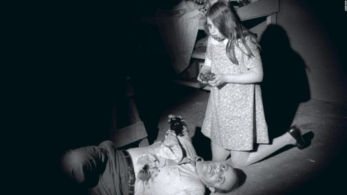 A man, one of his arms missing, lies dead on the floor while, kneeling next to him, a young girl (his daughter), blood smeared around her mouth, holds what appears to be a piece of the man's flesh that she is in the process of eating.